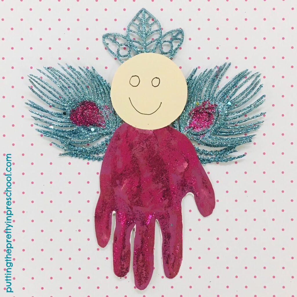 Christmas-themed handprint angel with glittery turquoise and magenta peacock-inspired wings.