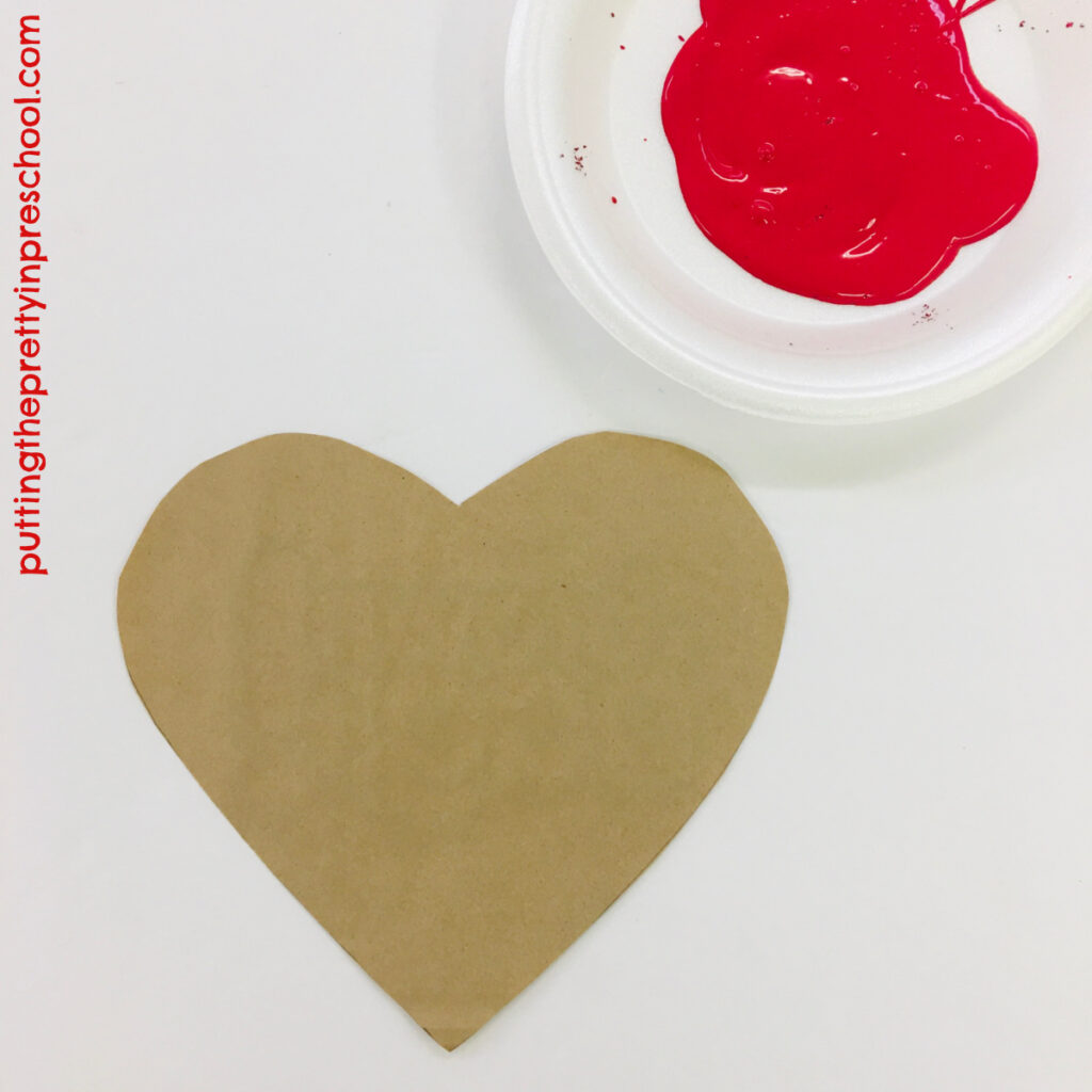 Invitation to make a red handprint on a paper bag heart.
