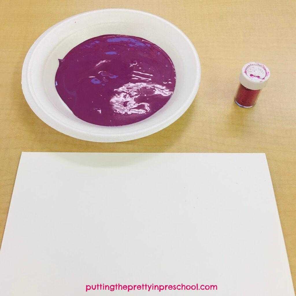 Invitation to make a magenta and pink glitter handprint.