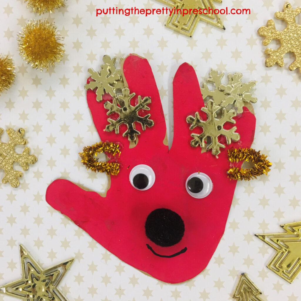 A red handprint turned into a friendly reindeer craft by adding snowflake antlers, wiggly eyes, pipe cleaner ears, and a pompom nose.