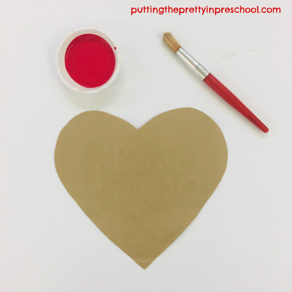 Invitation to paint a hand to make a print on a paper bag heart.