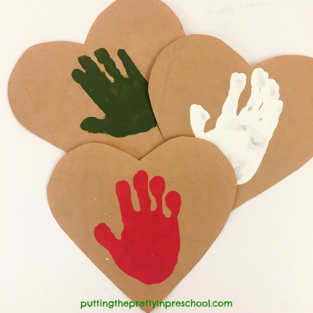 Paper bag hearts with red, green, and white handprints.