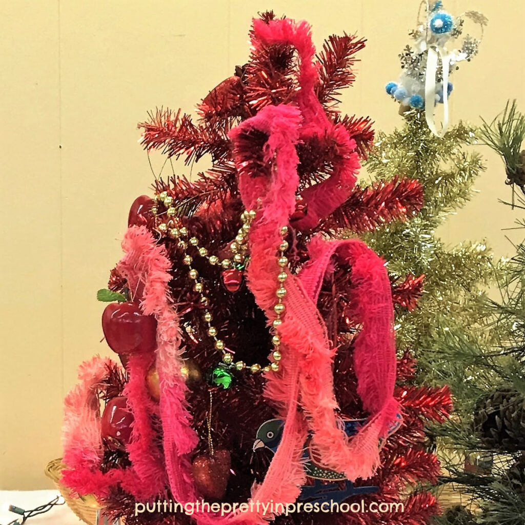 Red Christmas tree decorated with lots of garlands.
