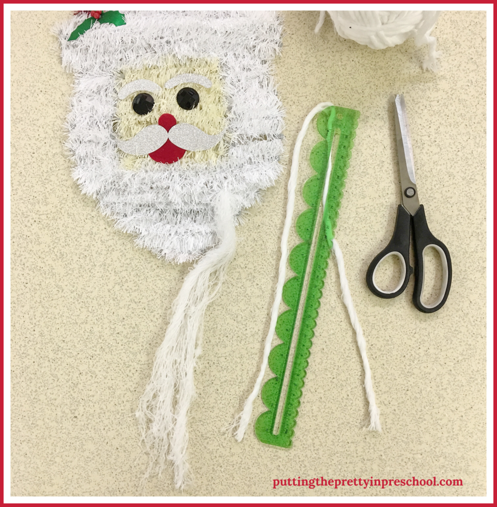 Cut strips of yarn in 60-cm/24-inch sections to string through Santa head wall decor. A scissor practice activity for young children.