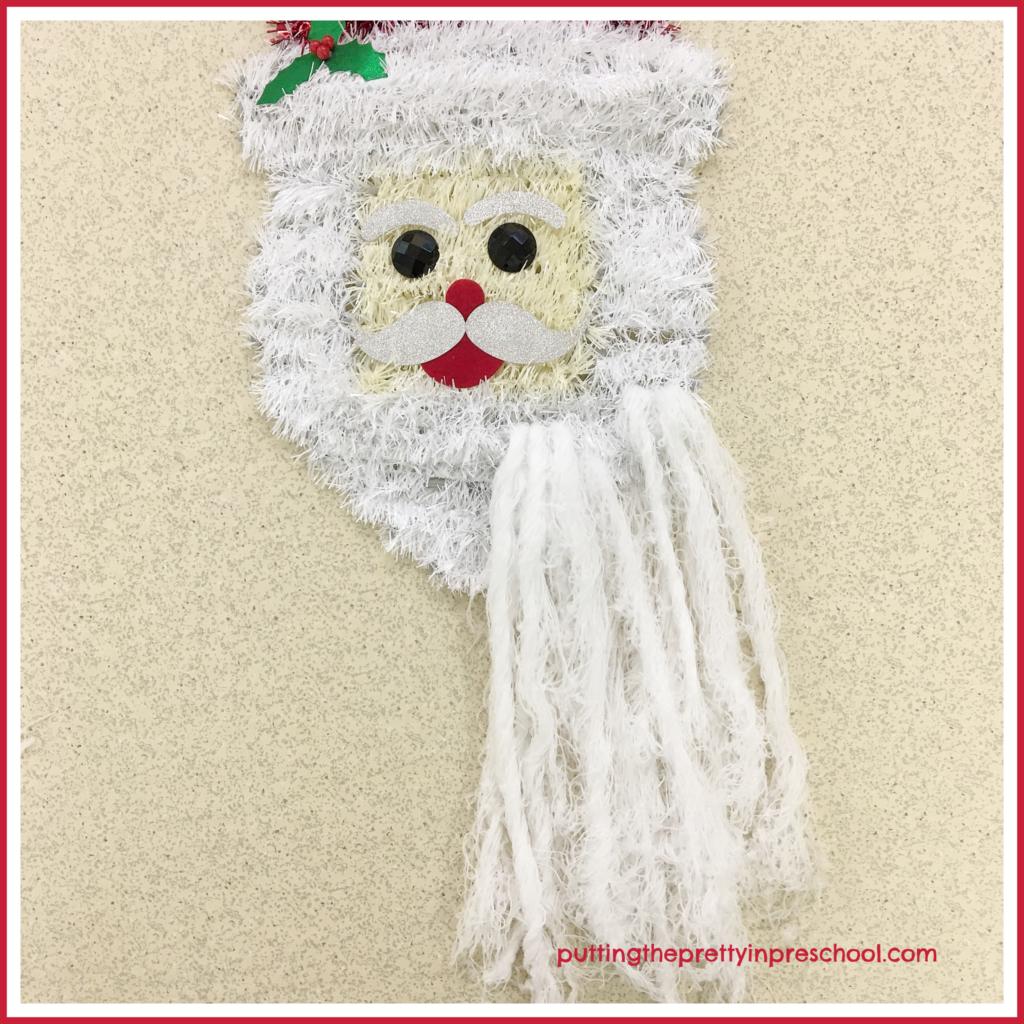 Repurpose Santa Head Wall Decor as a scissor skill activity. String white yarn to enhance Santa's beard and prepare it for cutting.