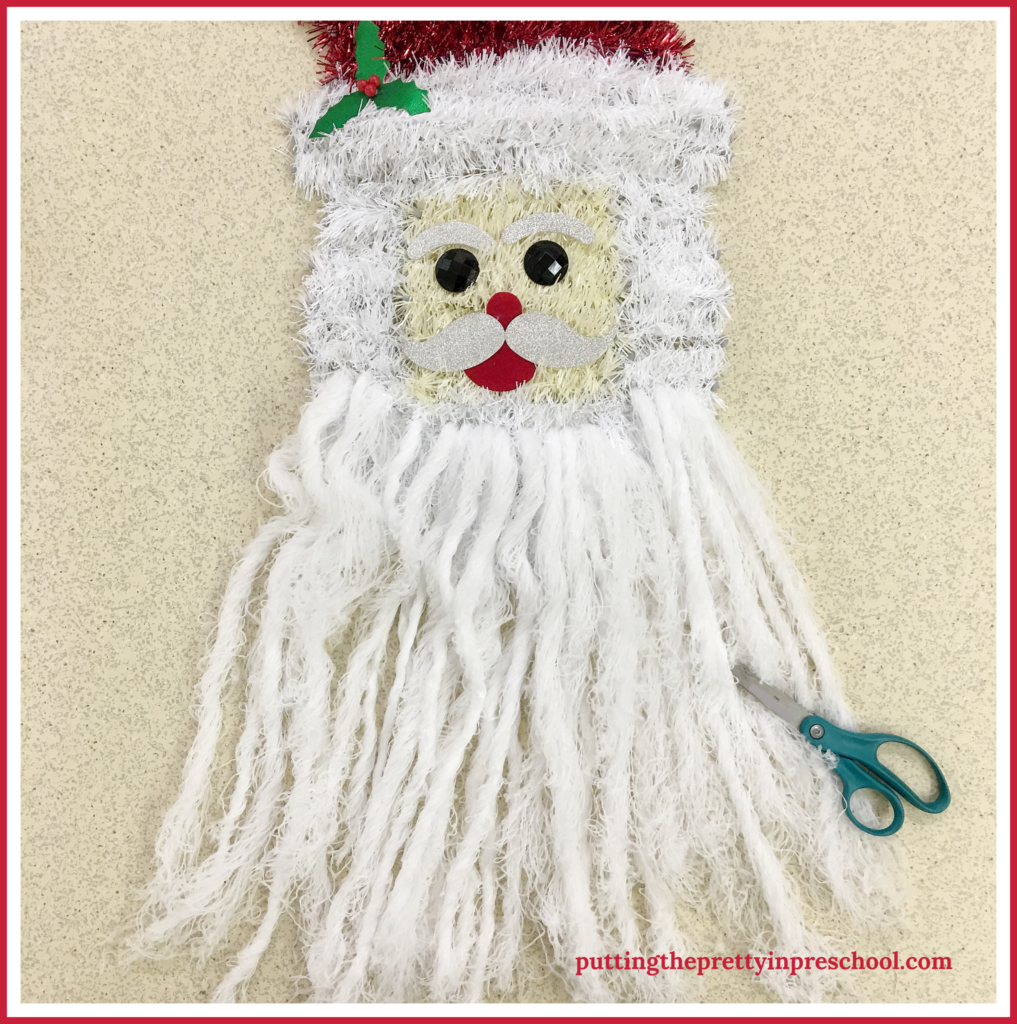An invitation to trim Santa's beard with repurposed wall decor. A scissor skill activity for young children.
