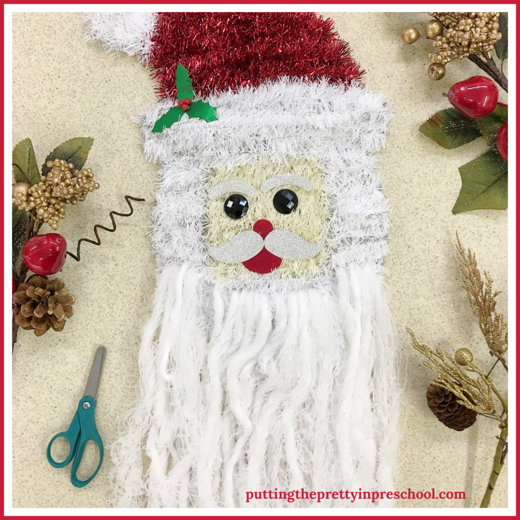 Santa head wall decor repurposed as a beard trimming scissor activity for young children. The white yarn is threaded through Santa's chin to add beard extensions perfect for cutting.