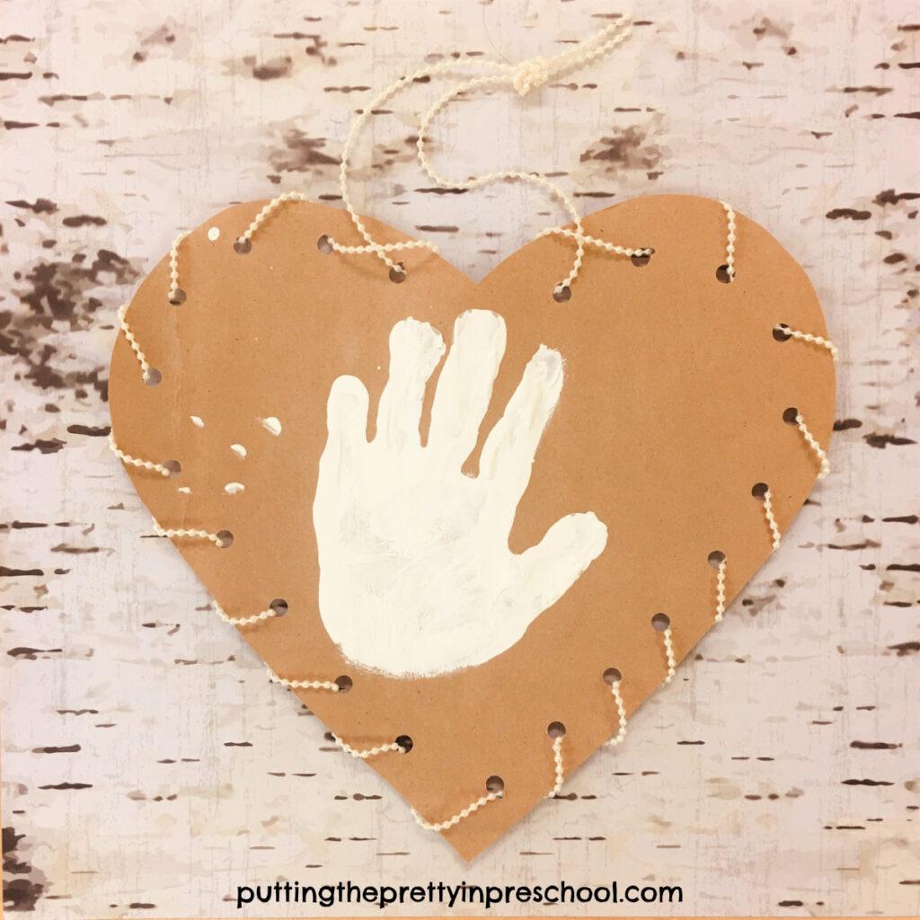 Bead garland laced white handprint heart craft.