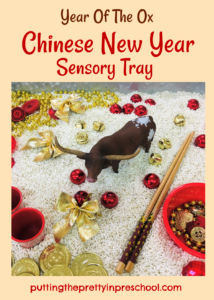 Year of the Ox Chinese New Year rice-based sensory tray with a bull figurine and red and gold loose parts.