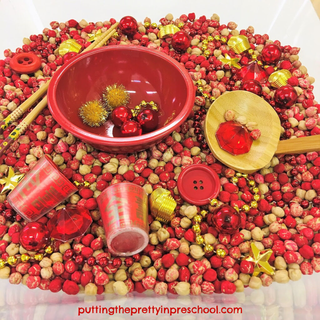 Red and gold accessories complement this chickpea-based Chinese New Year sensory tub.