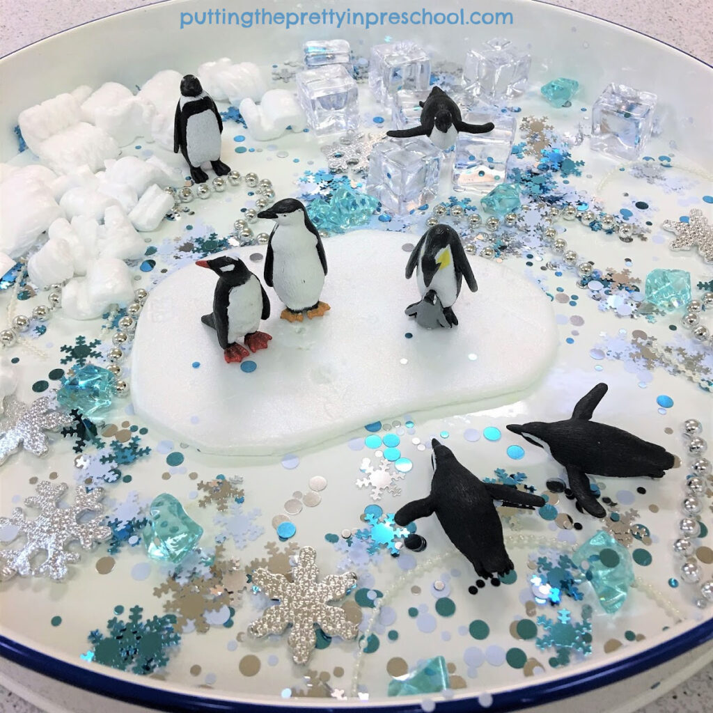 Penguin sensory tray with a snowflake confetti base.