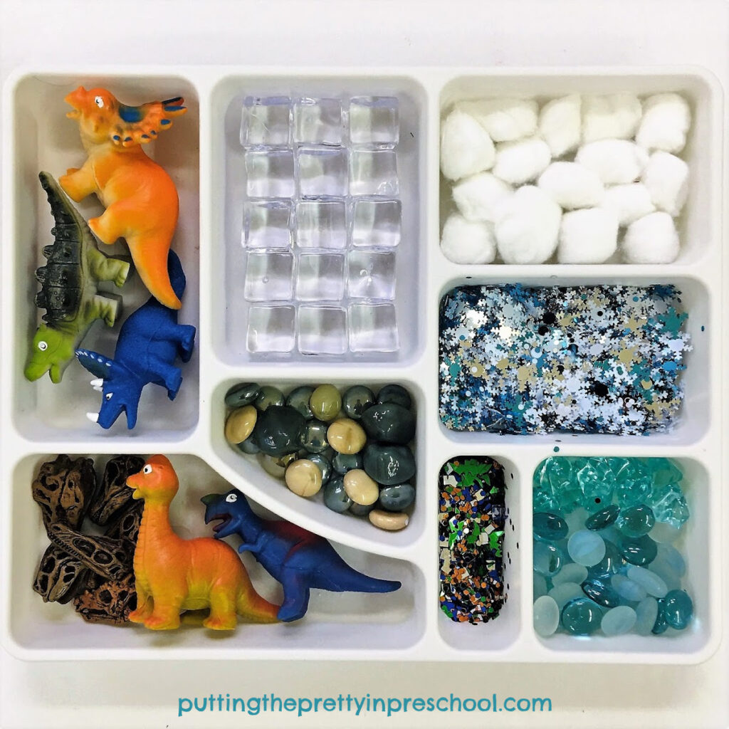 Loose parts tray featuring dinosaurs and winter-themed loose parts, perfect for exploring a polar dinosaur theme.