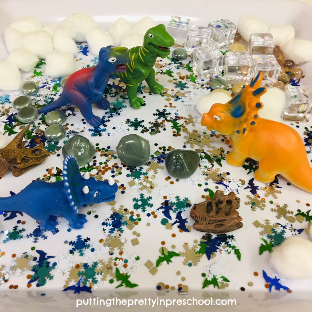 Polar dinosaur sensory play with dinosaurs and winter-themed loose parts.