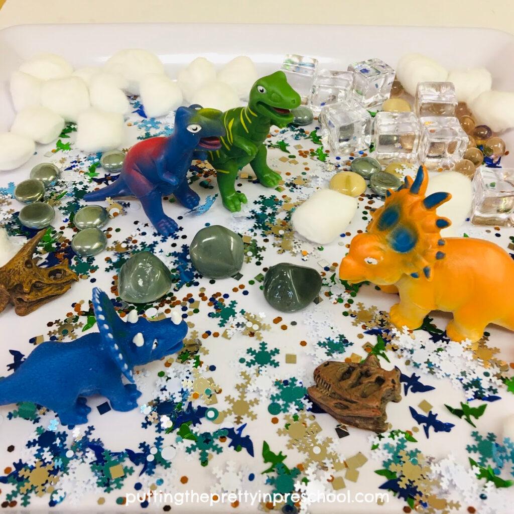 Polar dinosaur sensory tray with dinosaurs and winter-themed loose parts.