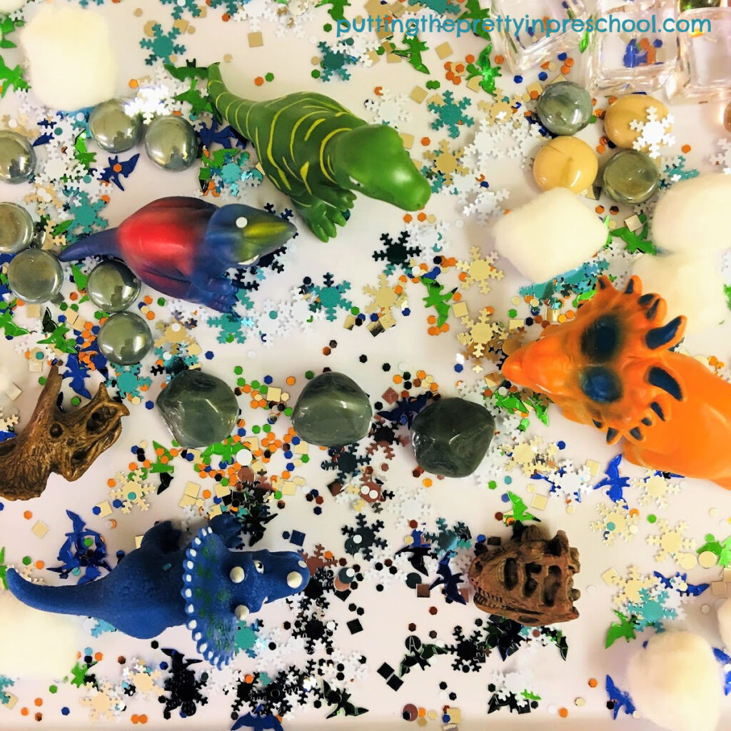 Sensory tray with dinosaurs and winter-themed loose parts, perfect for exploring a polar dinosaur theme.