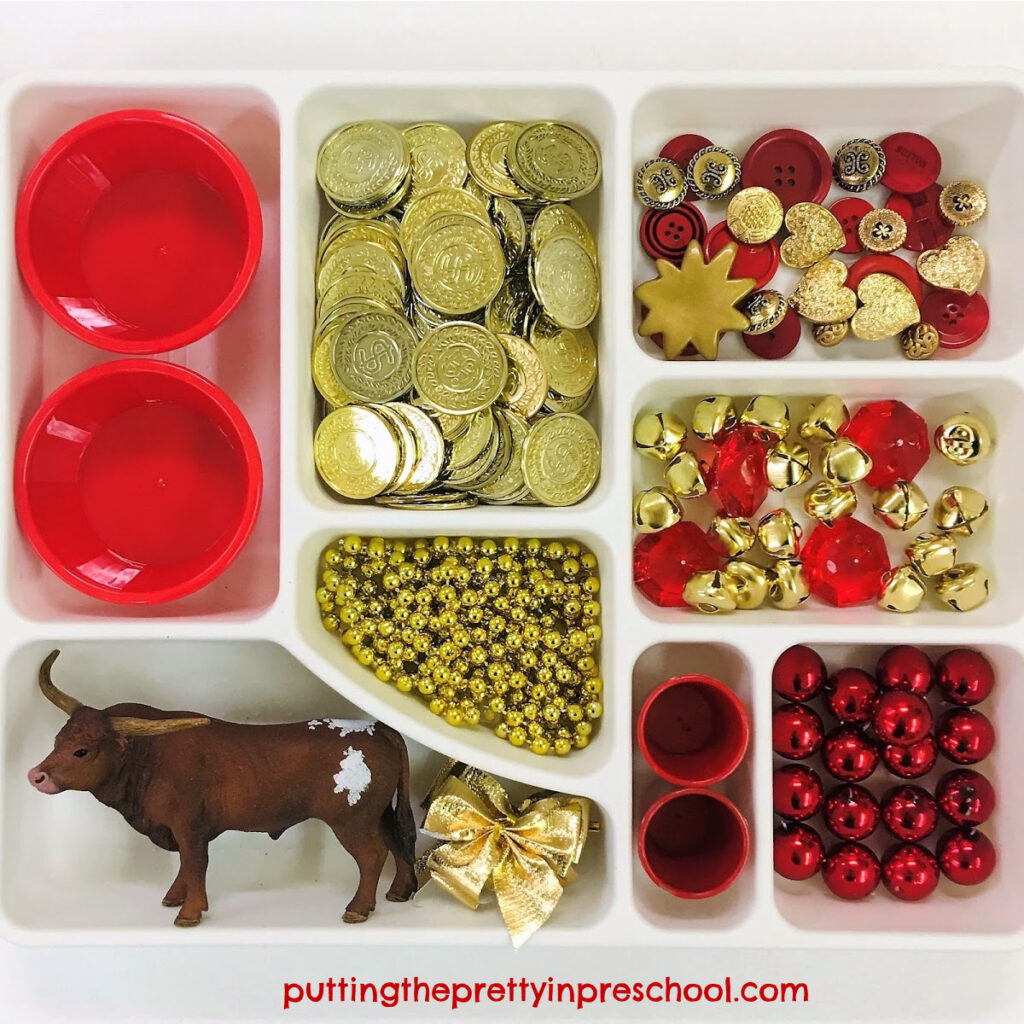 Chinese New Year loose parts tray featuring a bull figurine and red and gold loose parts.