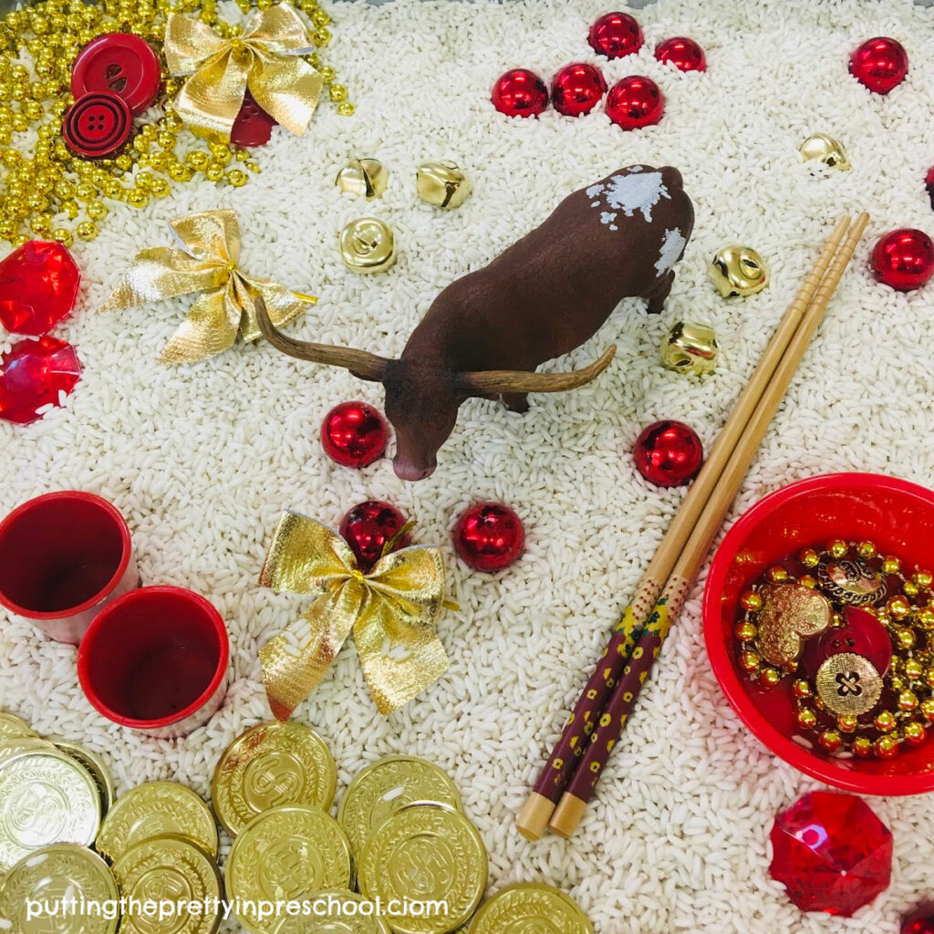 "Chinese New Year ""Year of The Ox"" rice-based tray featuring a bull figurine and red and gold loose parts."