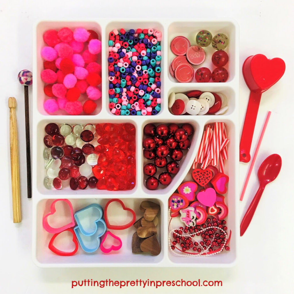 Loose parts to add to Valentine's Day containers to make shaker and drum musical instruments, and a variety of drumsticks.