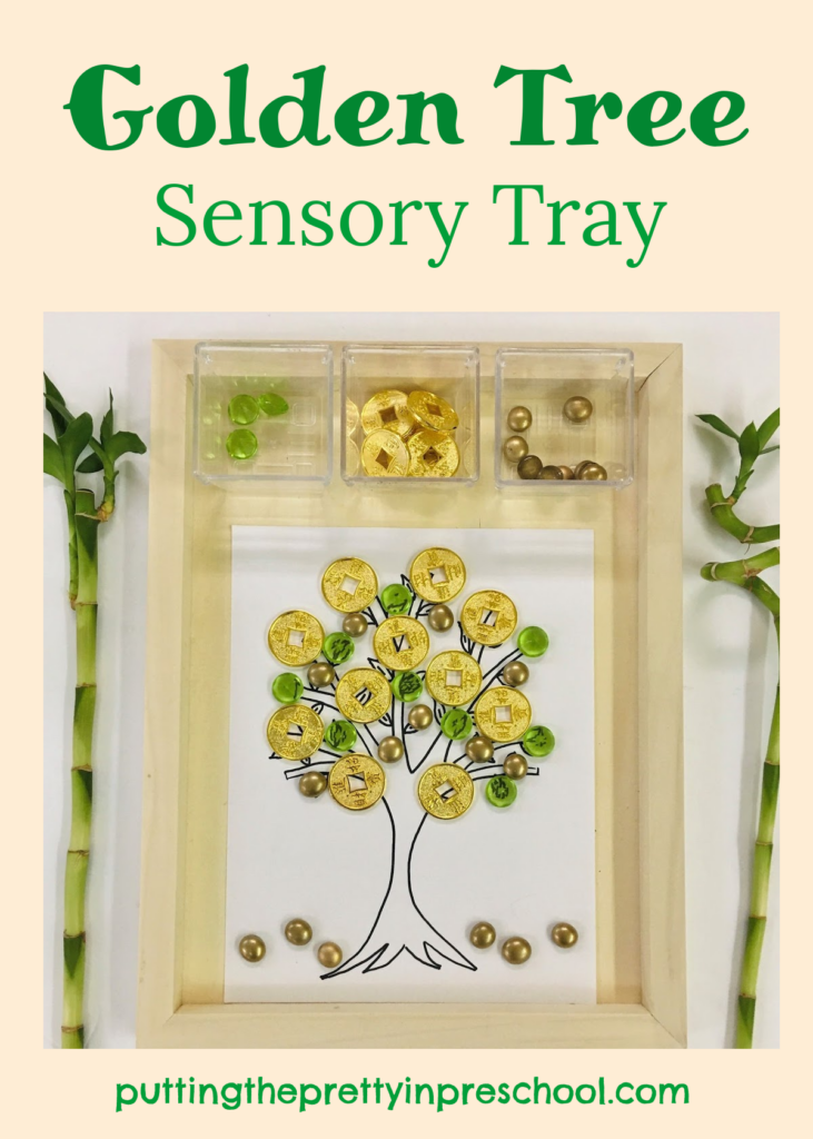 Golden tree sensory tray with coins and green and gold loose parts.