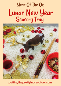 Year of the Ox Lunar New Year rice-based sensory tray with a bull figurine and red and gold loose parts.