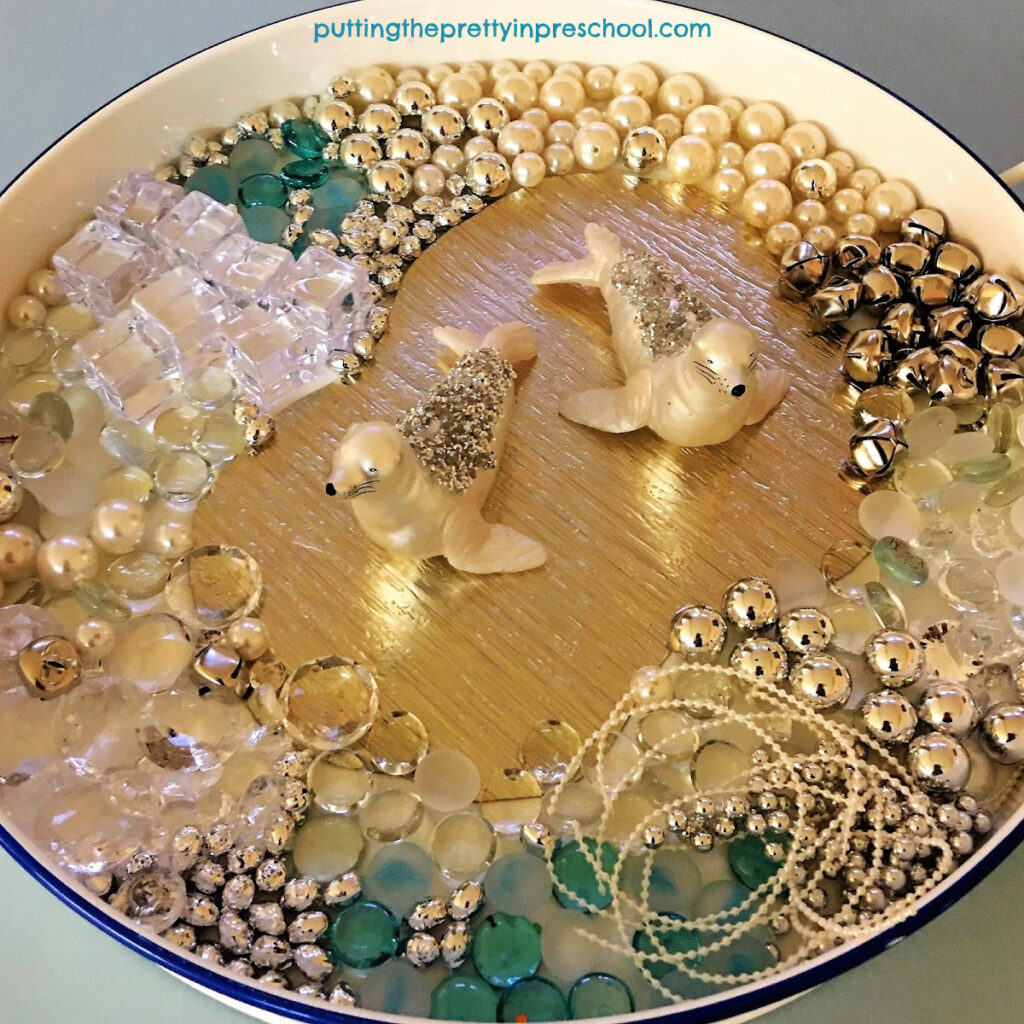 Glittery seals take center stage in this aquatic polar animal sensory tray.