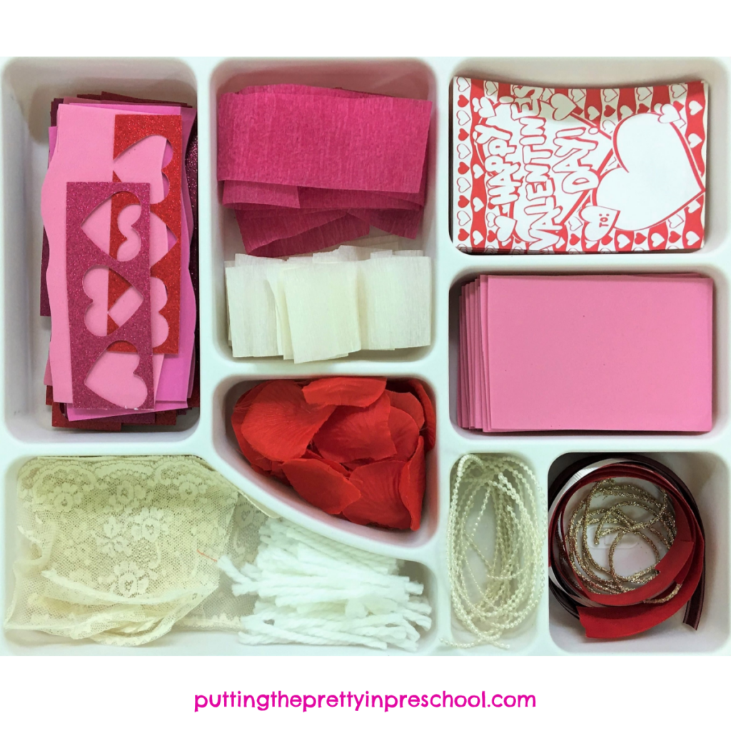 Red, pink, and white craft supply tray for heart collage projects.