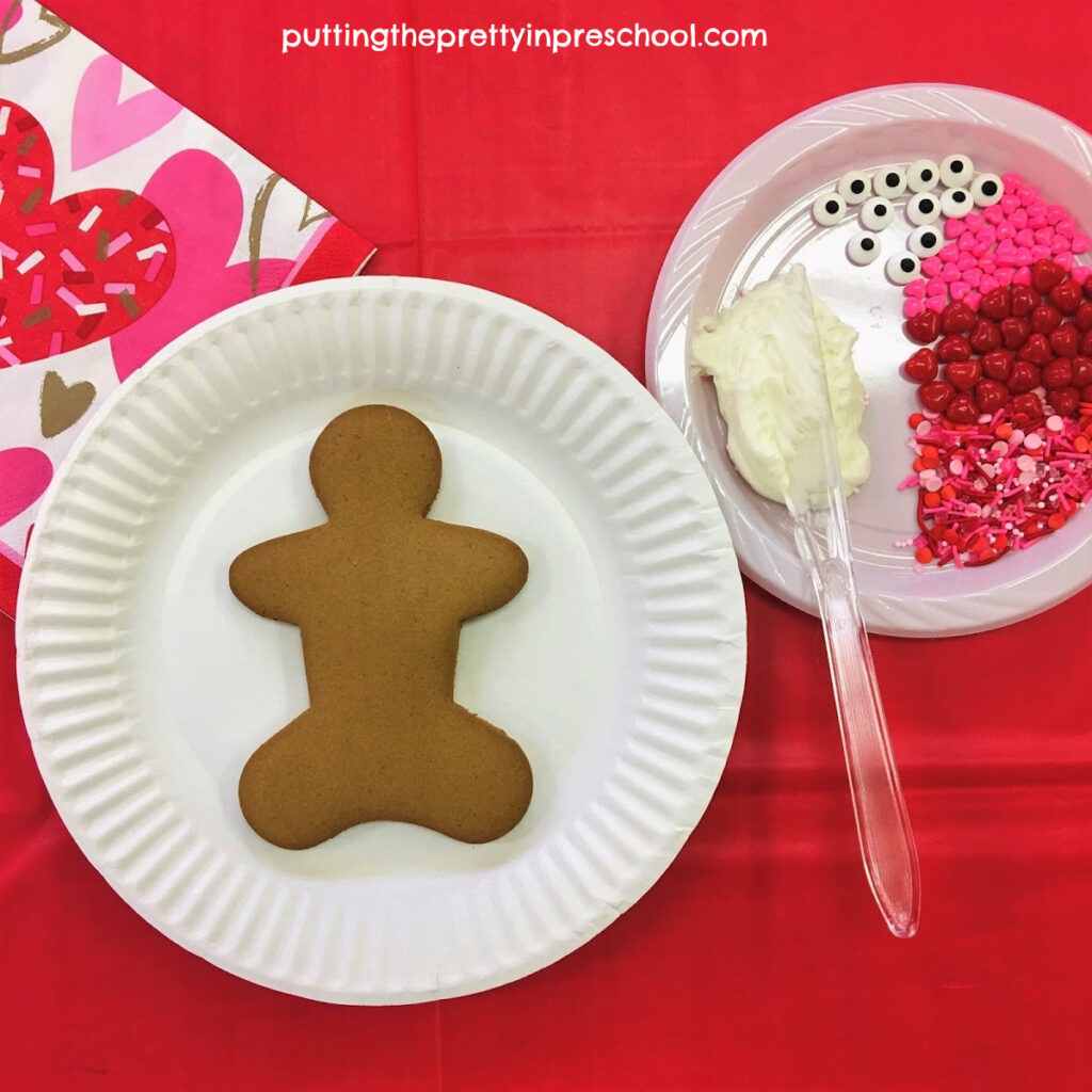 Gingerbread cookie decorating station with Valentine's Day-themed decorations.