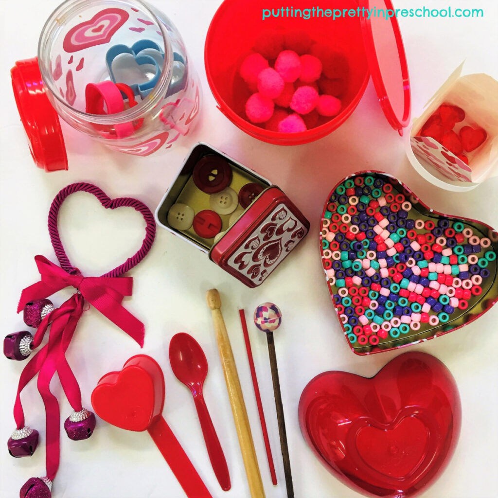 A collection of Valentine's Day-themed containers with loose parts and drumsticks for music-making.