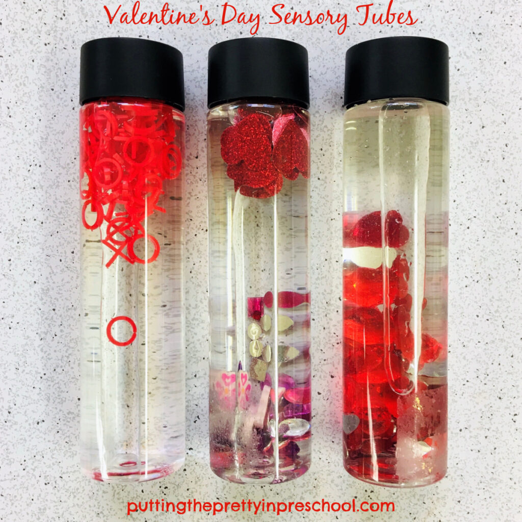 Valentine's Day sensory tubes with red, pink, and purple loose parts.
