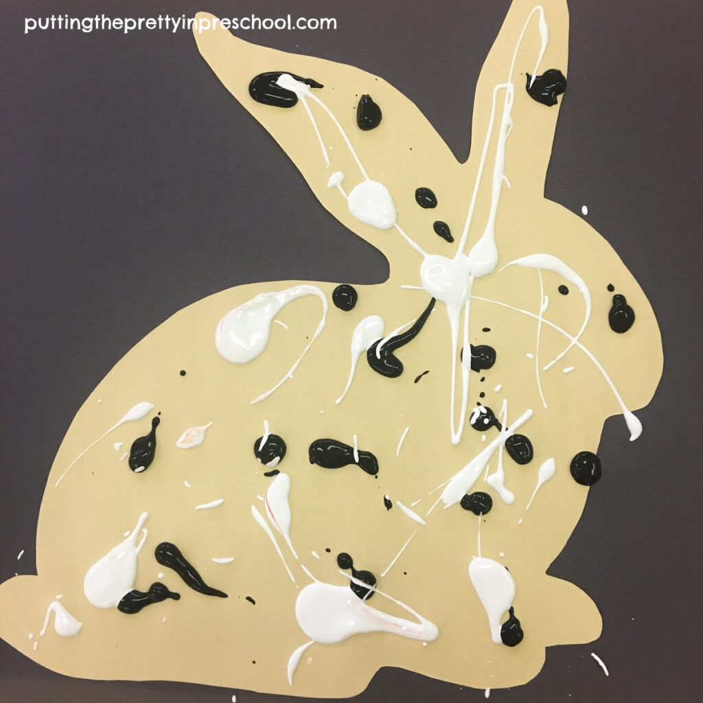 A spatter-painted paper bunny ready to be finished with a rolling pin painting technique.
