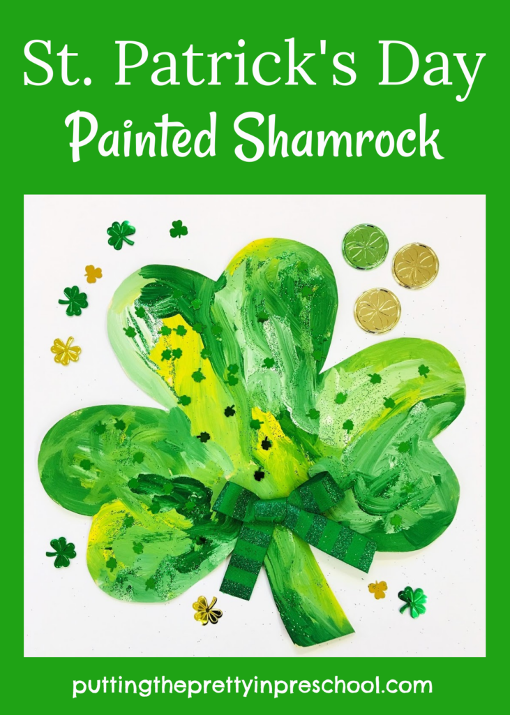 A painted shamrock sprinkled with green glitter and shamrock confetti. An all-ages art activity.