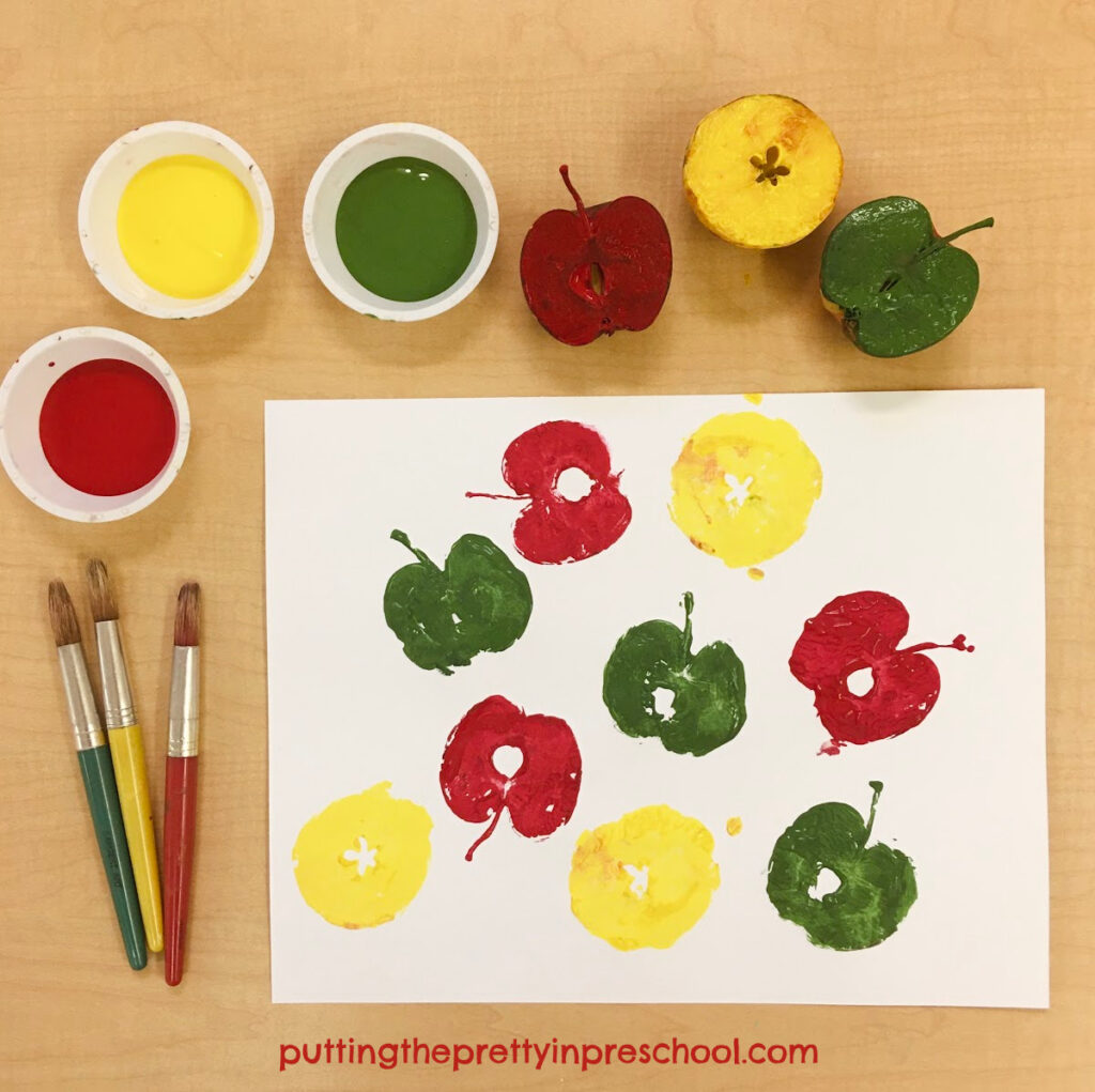 Apple printmaking with green, red, and yellow tempera paints.