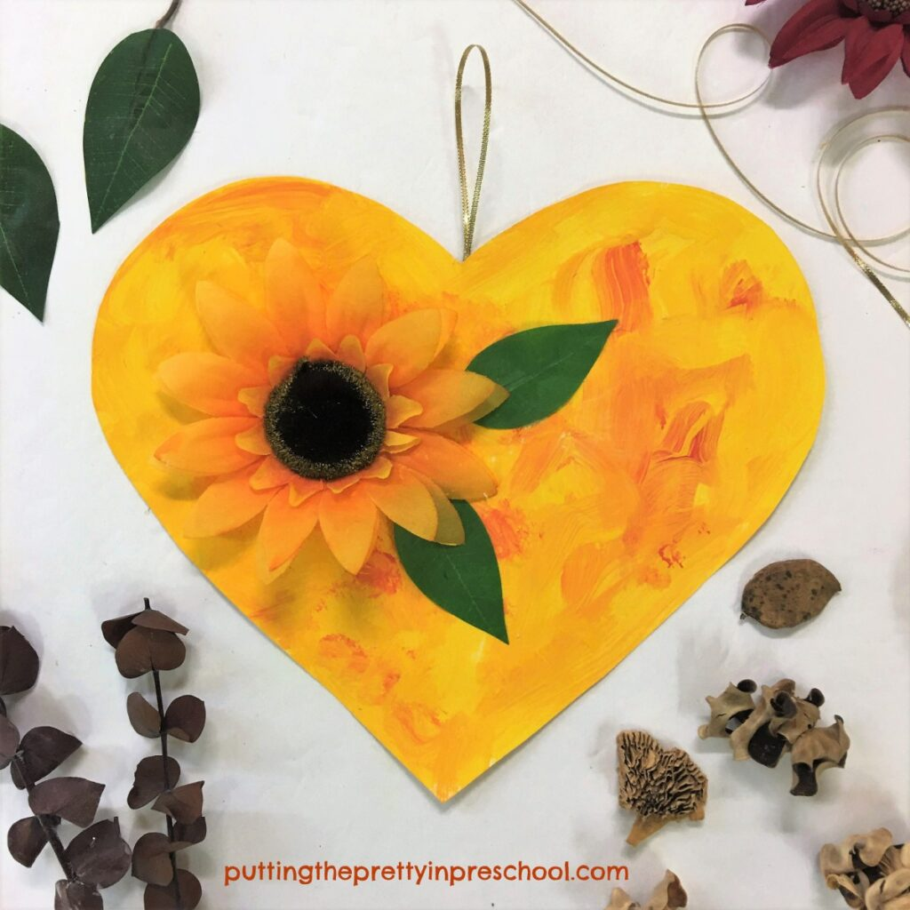 A painted heart embellished with a sunflower perfect for displaying in autumn.